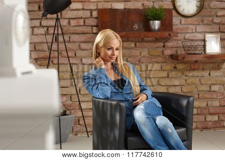Blonde woman sitting in armchair in retro home, daydreaming, looking away.