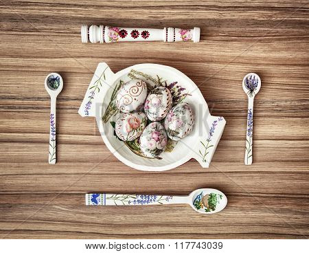 Decorative Wooden Bowl And Painted Easter Eggs With Spoons And Whistle On The Wooden Background