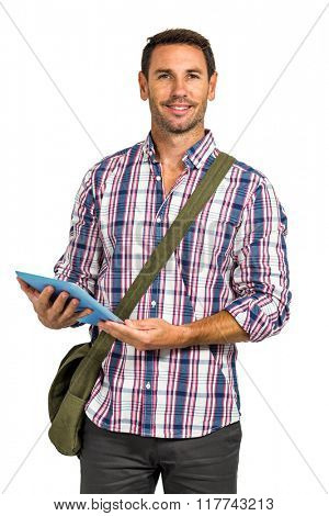 Smiling man with shoulder bag using tablet and looking at the camera on white screen