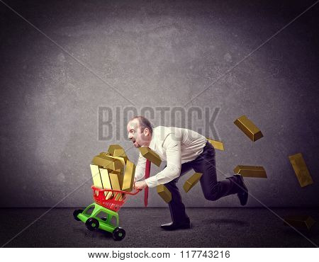 man with shopping troller toy and golden ingot