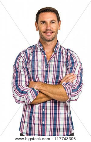 Portrait of smiling man with arms crossed on white screen