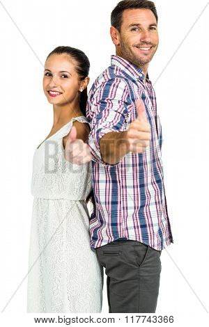Smiling couple standing back to back showing thumbs up on white screen