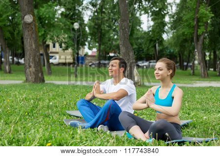 Young couple meditating on green grass