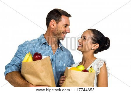 Smiling couple holding grocery bags on white screen