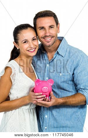 Excited couple holding piggybank on white screen