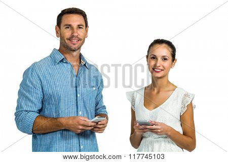 Smiling couple using smartphones and looking at camera on white screen