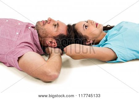 Couple relaxing on floor with hands on their heads on white screen