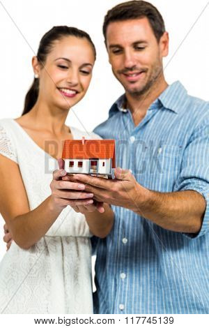 Young couple holding house model on white screen
