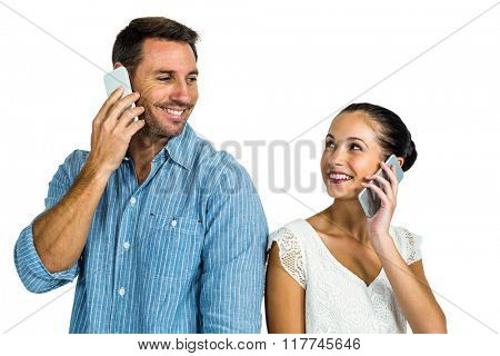 Smiling couple on phone call looking at each other on white screen