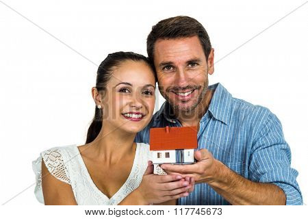 Excited couple holding house model on white screen