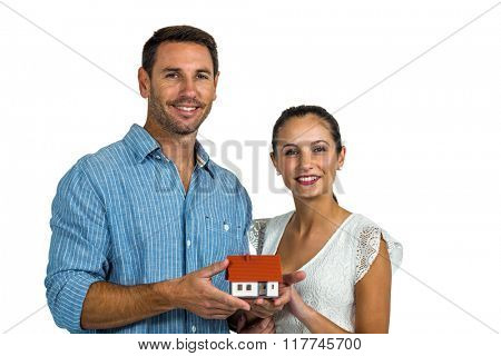 Man and woman holding house model on white screen