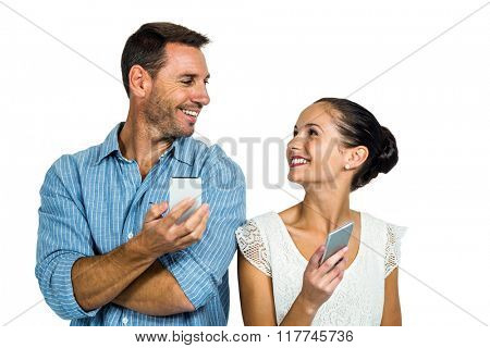 Happy couple using smartphones and looking at each other on white screen