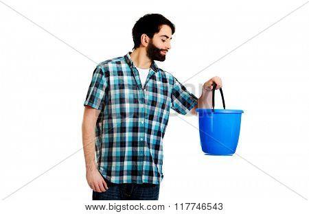 Handsome man looking into plastic bucket.