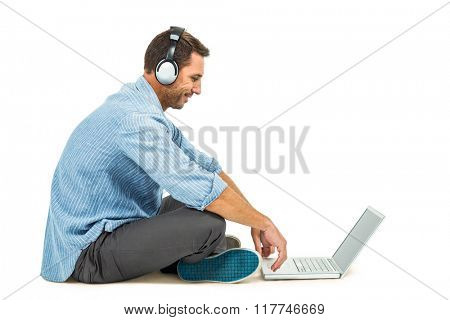 Smiling man sitting on floor using laptop and headphones on white screen