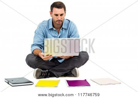 Man sitting on floor using laptop with notepads on floor on white screen