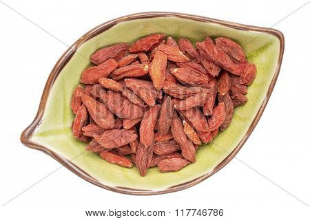 dried goji berries on an isolated leaf shaped ceramic bowl, top view
