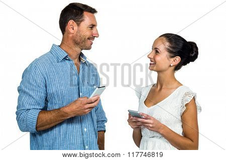 Smiling couple holding smartphones and looking at each other on white screen