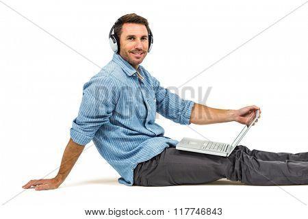 Happy man sitting on floor using laptop and headphones on white screen