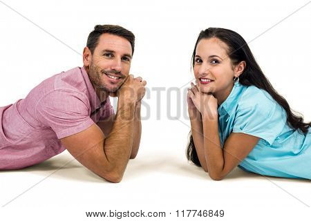 Smiling couple laying on the floor face to face looking at the camera on white screen