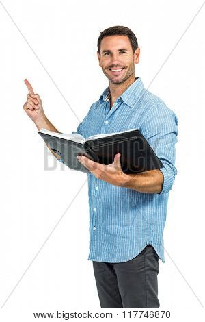 Smiling man holding a book and pointing up on white screen