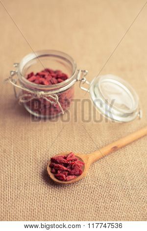 Dry red goji berries in wooden spoon on rustic background for a healthy diet.