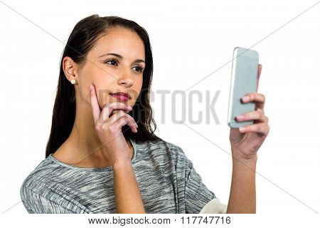 Thoughtful young woman using smartphone on white screen