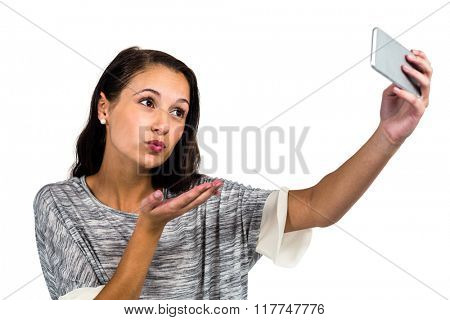 Woman blowing kiss while taking selfie on white screen