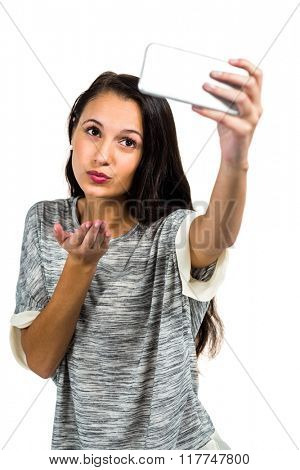 Young woman blowing kiss while taking selfie on white screen