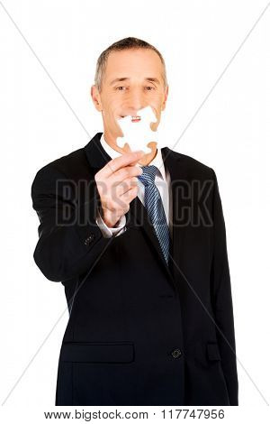Smart businessman holding a puzzle