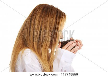 Woman in long sleeve shirt drinking coffee.