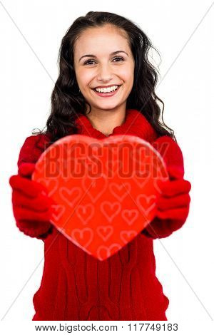 Smiling woman holding heart shape box on white screen