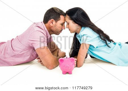 Couple laying on the floor face to face with piggybank on white screen