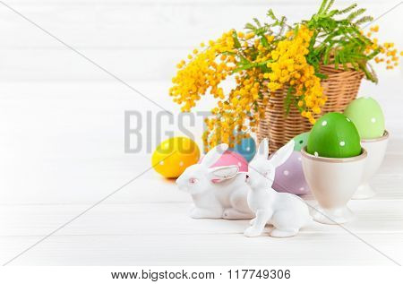 Easter eggs with white rabbits and branch mimosa on wooden board. Isolated on white background