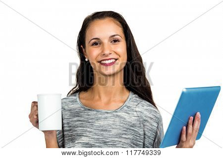 Smiling young woman holding cup and tablet on white screen