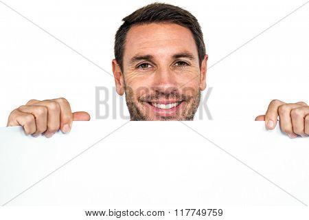 Smiling man holding blank sheet on white screen