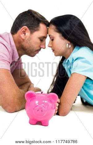 Worried couple laying on the floor face to face with piggybank on white screen