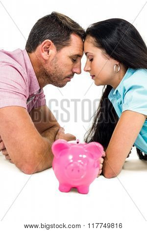 Young couple laying on the floor face to face with piggybank on white screen