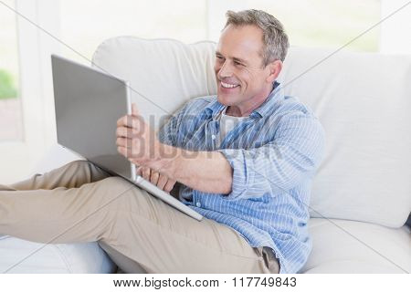 Happy man using laptop in the living room