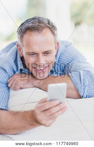 Happy man using smartphone in the living room