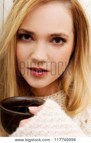 Beautiful woman drinking coffee in the kitchen.