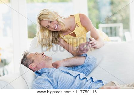 Happy couple using smartphone in the living room