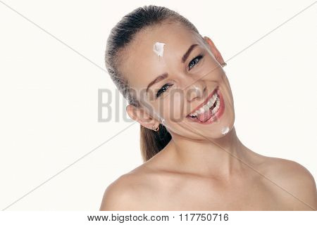 Girl Smeared A Cream Face And Smiles Broadly, Showing Tongue.