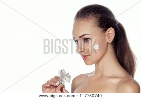 Girl Smeared Face Cream. She Is Standing In Profile And Holding A Lily Flower.