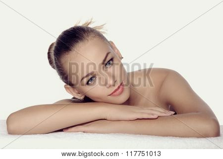 Girl Lies On A Towel In A Spa. She Looks Very Pleased And Relaxed.