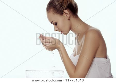 Girl Washes Her Face, Leaning Over A Bowl, And With Her Hands Dripping Water.