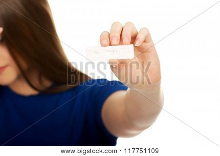 Unhappy woman holding pregnancy test.