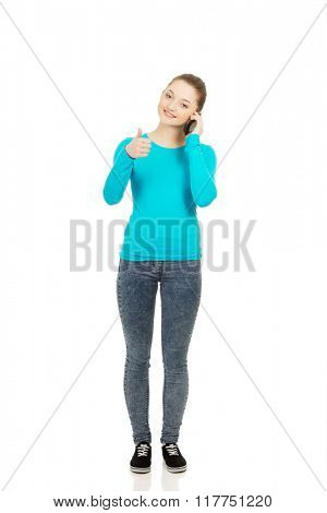 Teen with mobile phone and thumbs up.