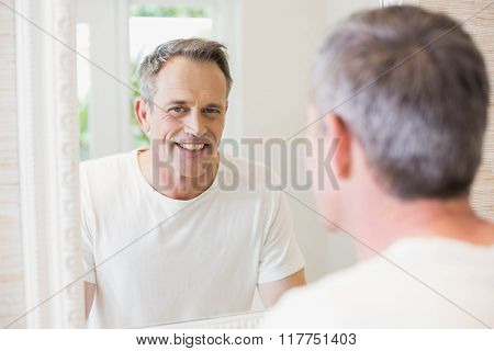 Handsome man looking at himself in the mirror in the bathroom