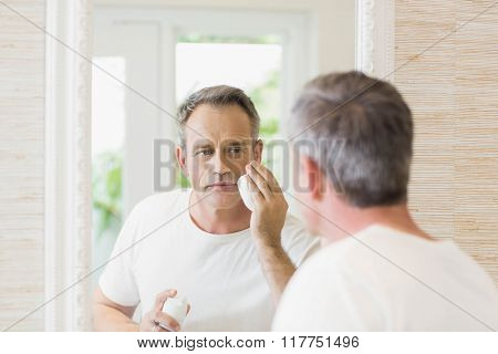 Handsome man applying shaving foam in the bathroom