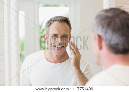 Handsome man applying shaving foam in the bathroom